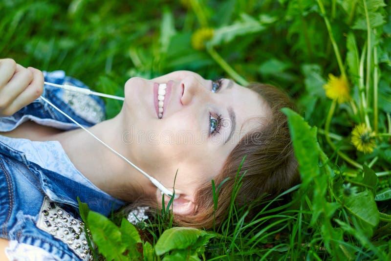 Avkopplad kvinna som lyssnar till musiken med hörlurar som ligger på gräset arkivbilder