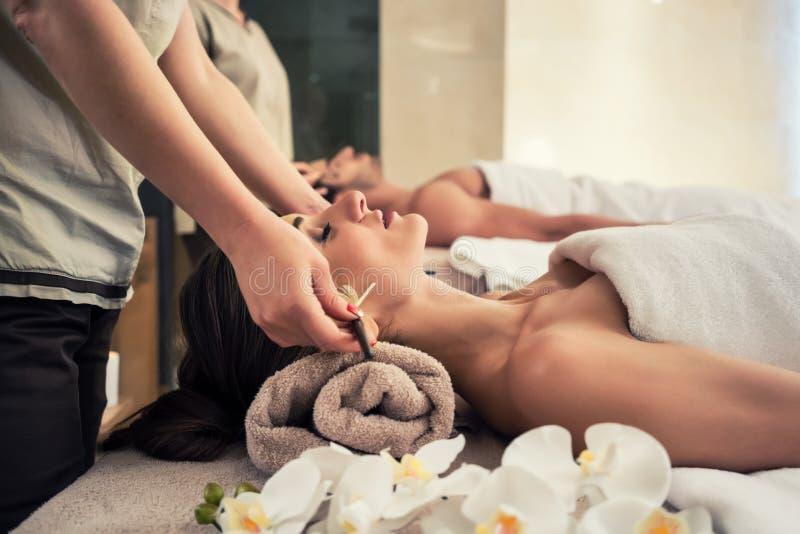 Avkopplad kvinna som ner ligger på massagesäng under ansikts- behandling royaltyfri fotografi