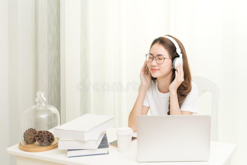 Avkopplad le kvinna i hörlurar som tycker om bra musik genom att använda bärbara datorn app, i coworking som hemma tycker om tid fotografering för bildbyråer