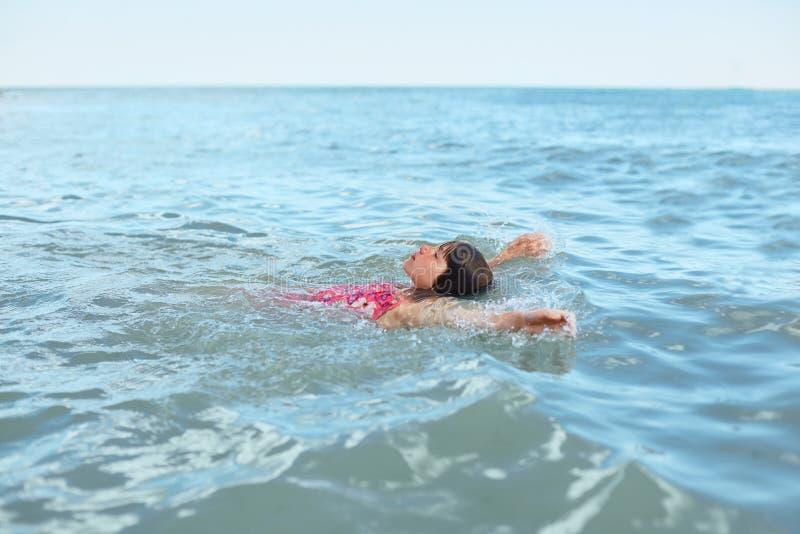 Avkopplad liten flicka i baddräkten som tillbaka ligger på henne och att simma i det djupa havet och att tycka om landskap som se royaltyfria foton