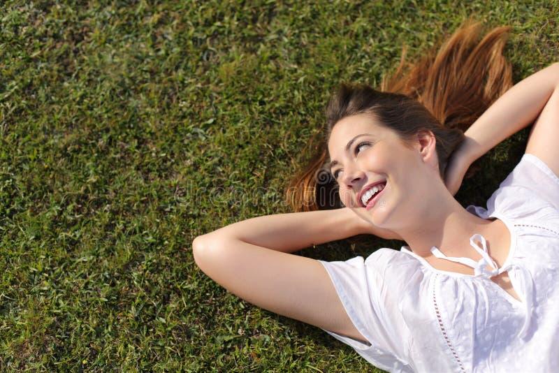 Avkopplad lycklig kvinna som vilar på gräset som ser sidan royaltyfria bilder