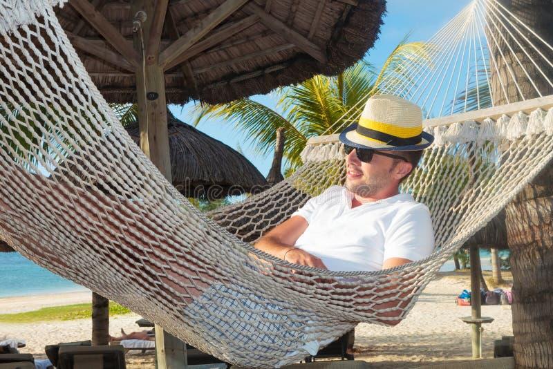 Avkopplad man i en hängmatta på stranden royaltyfria foton