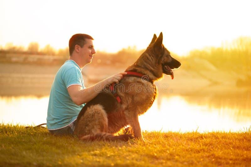 Avkopplad man och hund som tycker om sommarsolnedgång eller soluppgång arkivbild