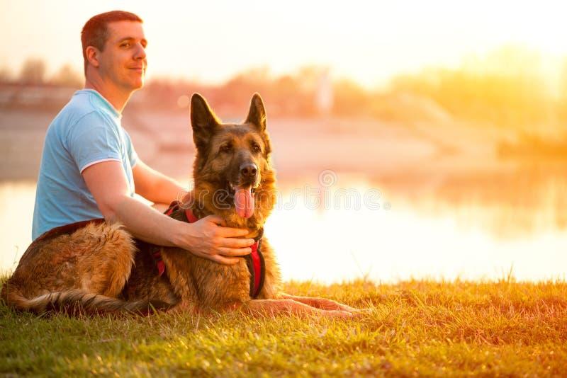 Avkopplad man och hund som tycker om sommarsolnedgång eller soluppgång arkivfoto