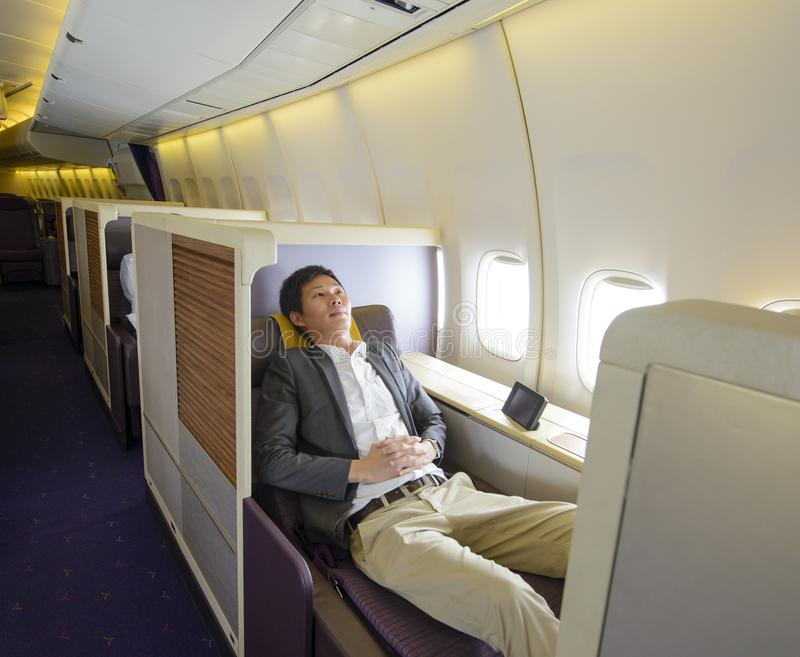 Avkopplad mitt- vuxen affärsman som sover i första klassplats royaltyfri foto