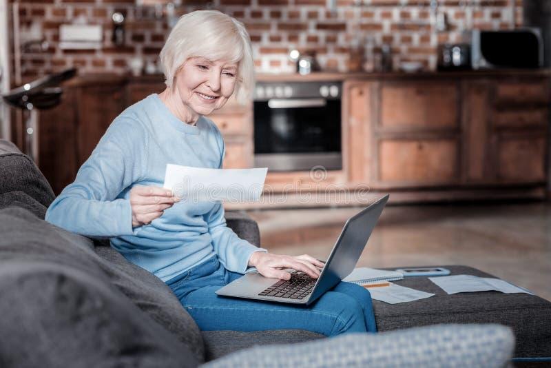 Avkopplad mogen kvinna som arbetar med datoren royaltyfria bilder