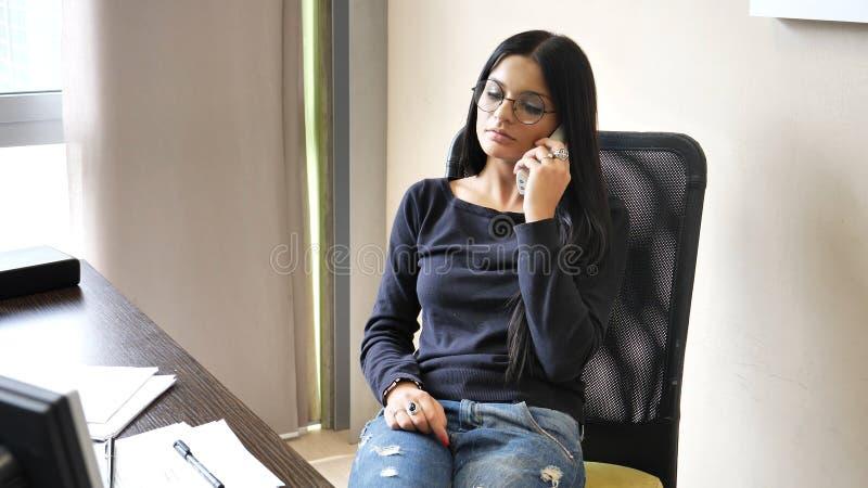 Avkopplad nätt ung affärskvinna på skrivbordet på telefonen royaltyfri foto
