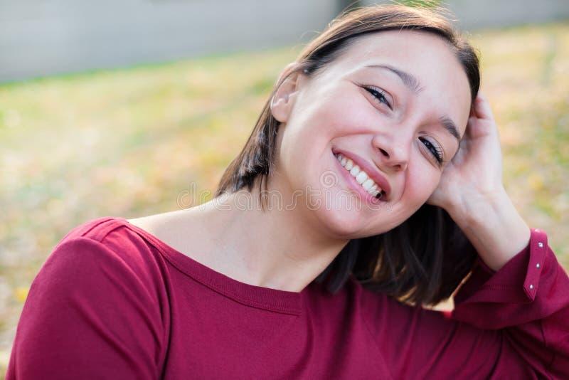 Avkopplad och gladlynt ung caucasian kvinnastående arkivbild