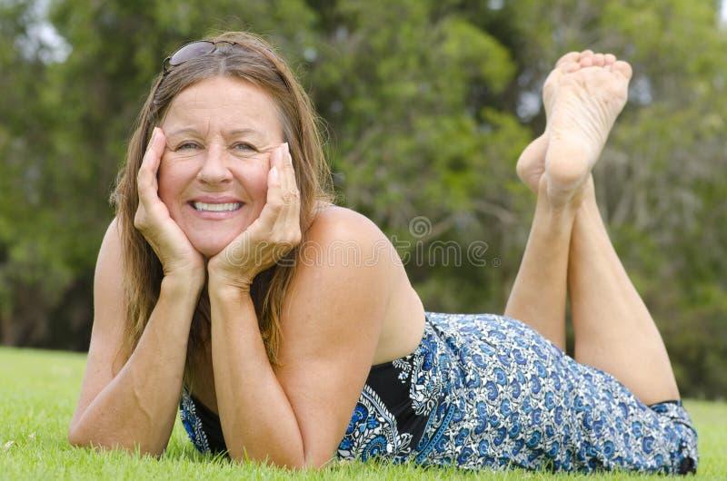 Avkopplad rest för härlig mogen kvinna i park arkivfoton