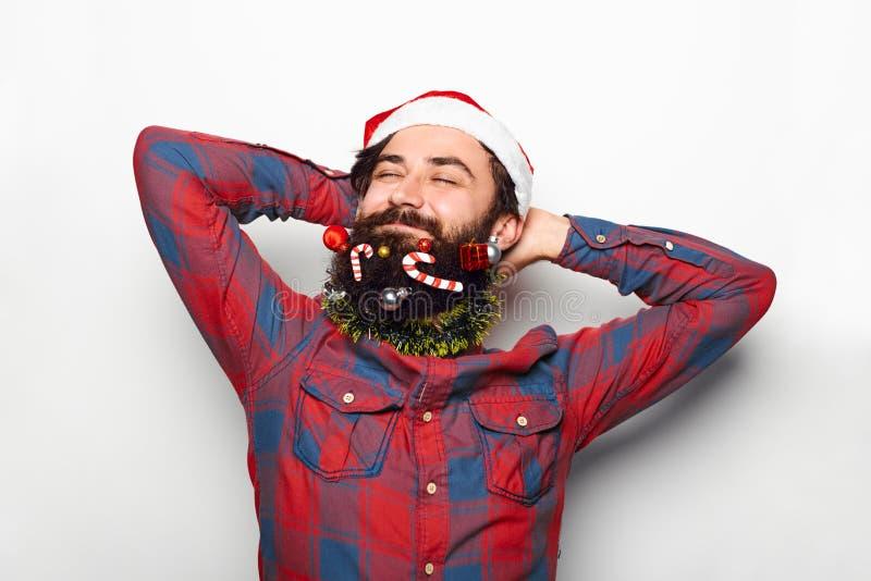 Avkopplad skäggig man i den julsanta hatten arkivfoton