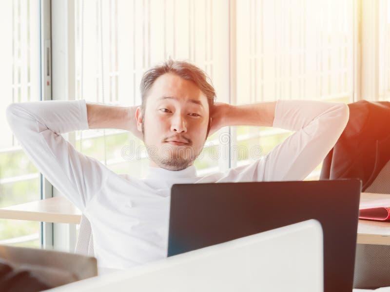 Avkopplad tillfällig ung man som arbetar på bärbara datorn fotografering för bildbyråer