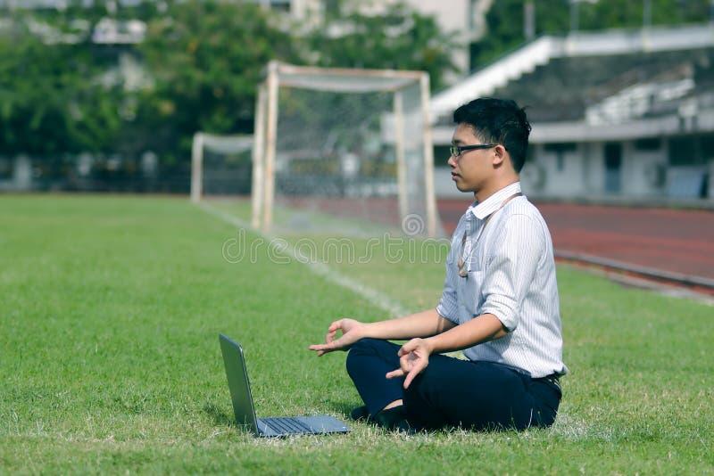 Avkopplad ung asiatisk affärsman med bärbara datorn som gör yogaposition på det gröna gräset av stadion fotografering för bildbyråer