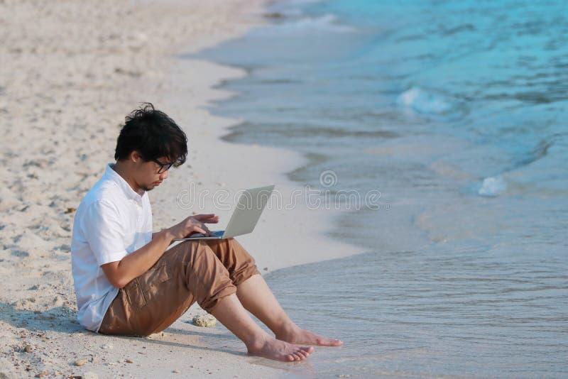 Avkopplad ung asiatisk man med bärbara datorn som sitter på sandigt av stranden Internet av sakerbegreppet royaltyfria foton