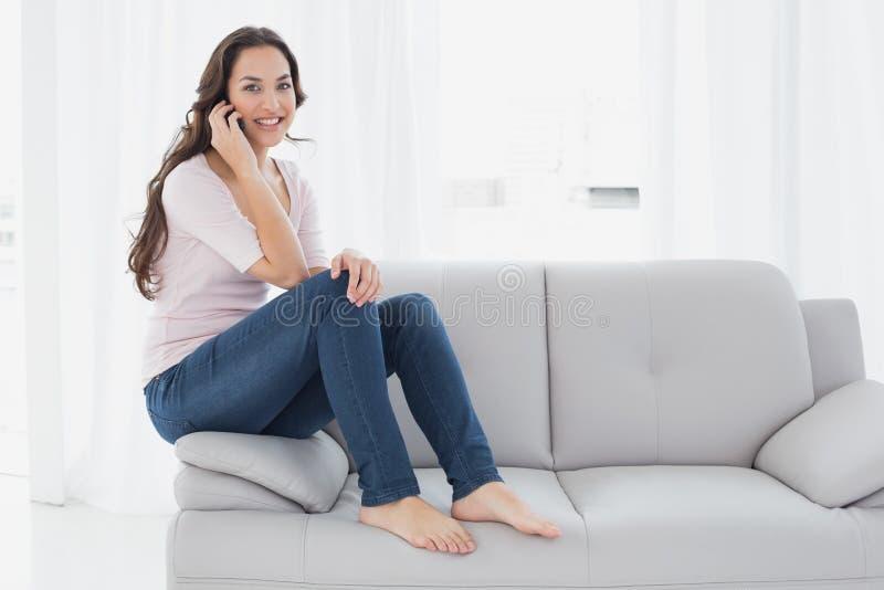 Avkopplad ung kvinna som hemma använder mobiltelefonen på soffan arkivbilder