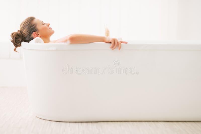 Avkopplad ung kvinna som lägger i badkar arkivfoton