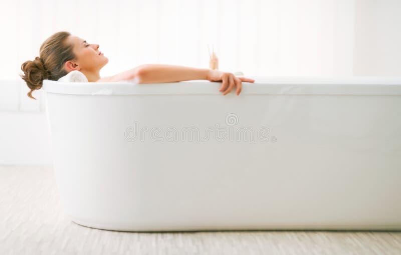 Avkopplad ung kvinna som lägger i det vita badkaret royaltyfria foton