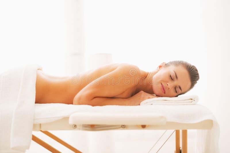 Avkopplad ung kvinna som lägger på massagetabellen royaltyfri fotografi