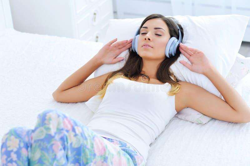 Avkopplad ung kvinna som lyssnar till musik i hörlurar royaltyfri fotografi