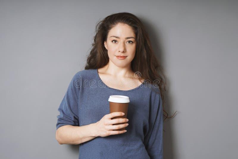 Avkopplad ung kvinna som rymmer kaffe för att gå i disponibel kopp fotografering för bildbyråer