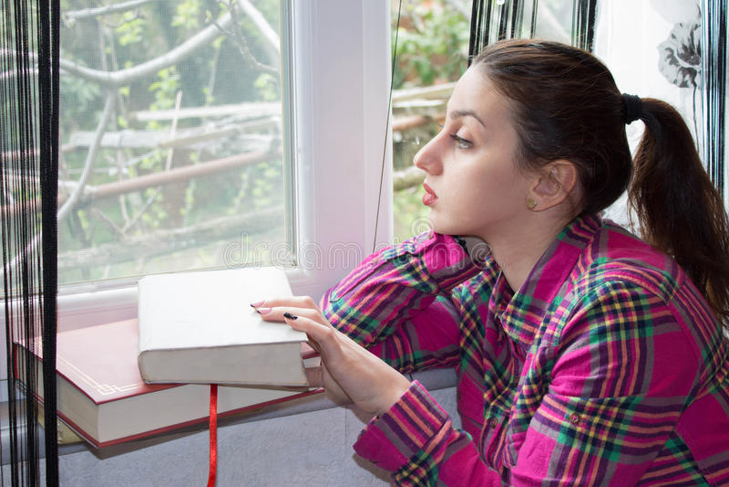 Avkopplad ung kvinna som sitter nära fönster med en bok royaltyfri fotografi
