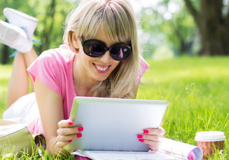 Avkopplad ung kvinna som utomhus använder minnestavladatoren royaltyfria bilder