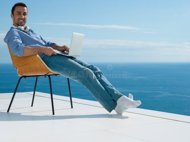 Avkopplad ung man hemma på balkong arkivfoto