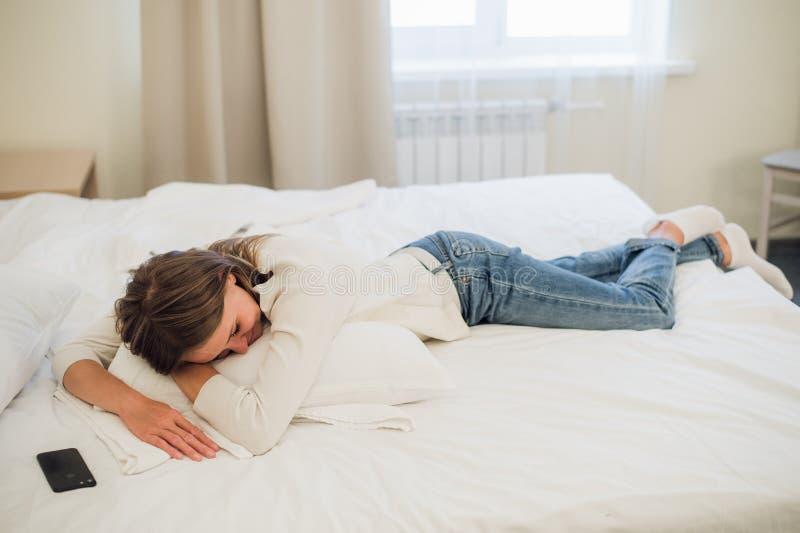Avkopplad ung nätt kvinna som sover i säng med mobiltelefonen för tom skärm royaltyfri fotografi