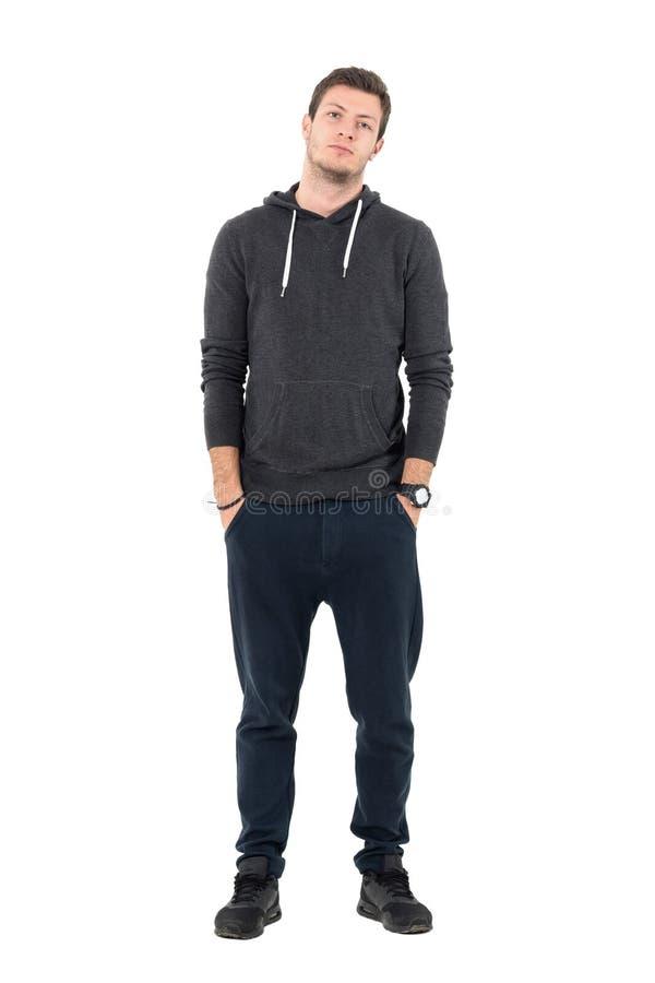 Avkopplad ung sportig man i med huva tröja och sweatpants som ser kameran arkivfoto