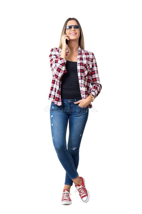 Avkopplad ung tillfällig kvinna i jeans och plädskjorta som talar på le för telefon fotografering för bildbyråer