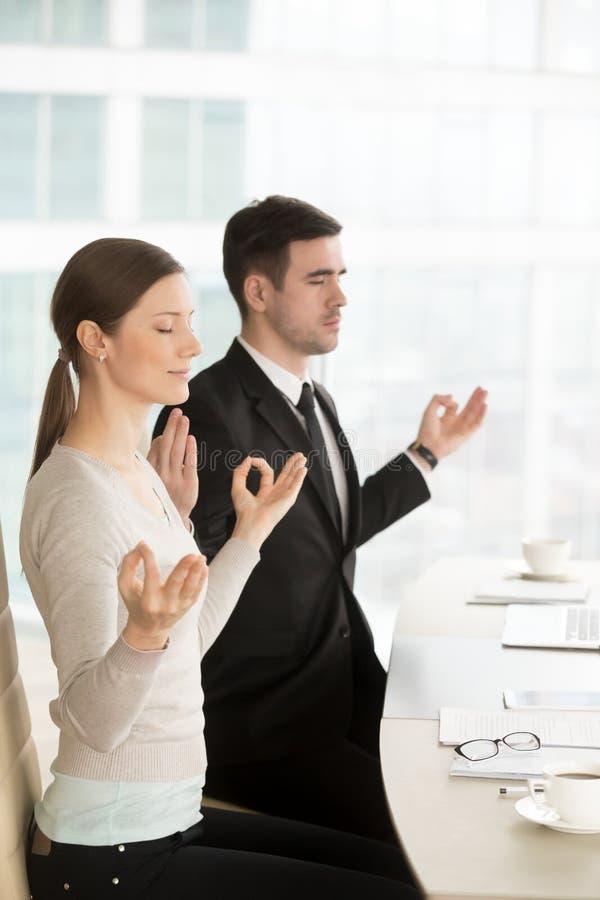 Avkopplad uppmärksam affärsman och affärskvinna som mediterar på arbete royaltyfria foton