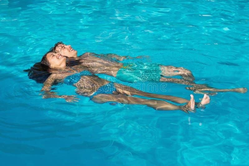Avkopplade barnpar i simbassäng fotografering för bildbyråer