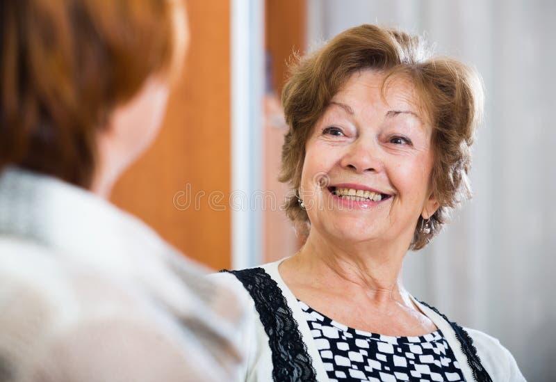 Avkopplade kvinnliga pensionärer som inomhus pratar och ler royaltyfria foton