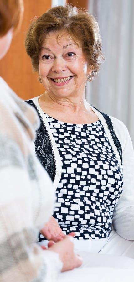 Avkopplade kvinnliga pensionärer som inomhus pratar och ler royaltyfria bilder