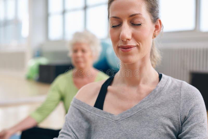 Avkopplade kvinnor i meditation på idrottshallen fotografering för bildbyråer