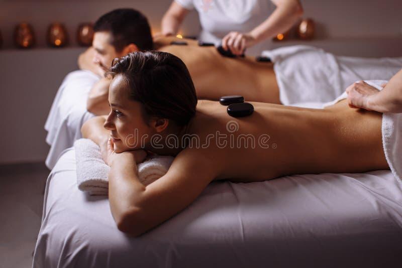 Avkopplade par som mottar varm stenterapi på skönhet Spa arkivfoto