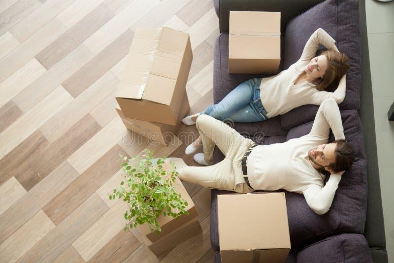 Avkopplade par som vilar på soffan efter nytt hem för inflyttning arkivfoton