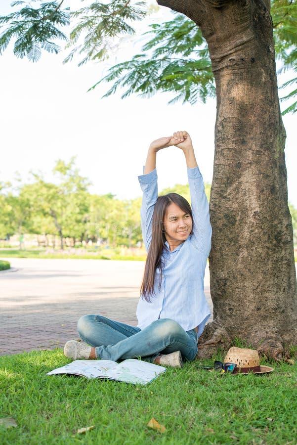 Avkopplade unga härliga kvinnakläder en blå skjorta med att le framsidan på parkera royaltyfri fotografi