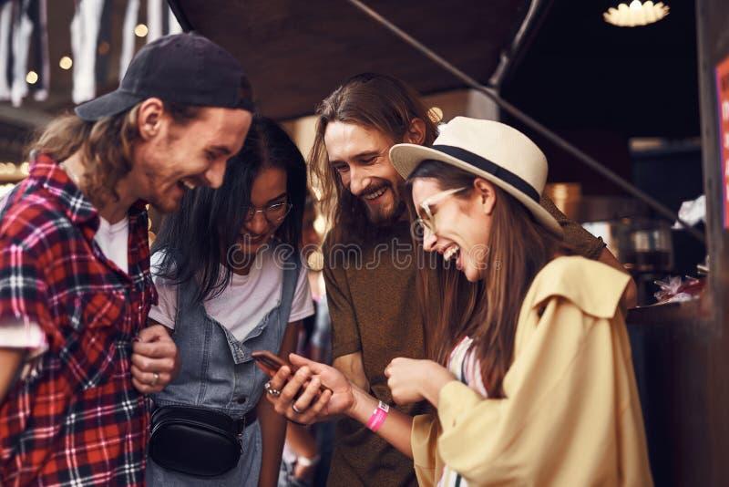 Avkopplat folk som skrattar, medan läsa roliga skämt i smartphonen royaltyfri fotografi
