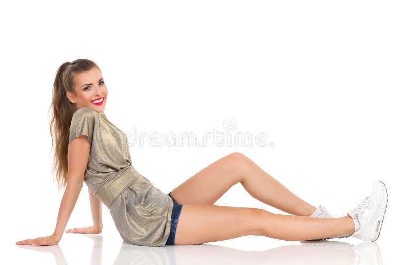 Avkopplat sammanträde för ung kvinna på ett golv royaltyfria bilder