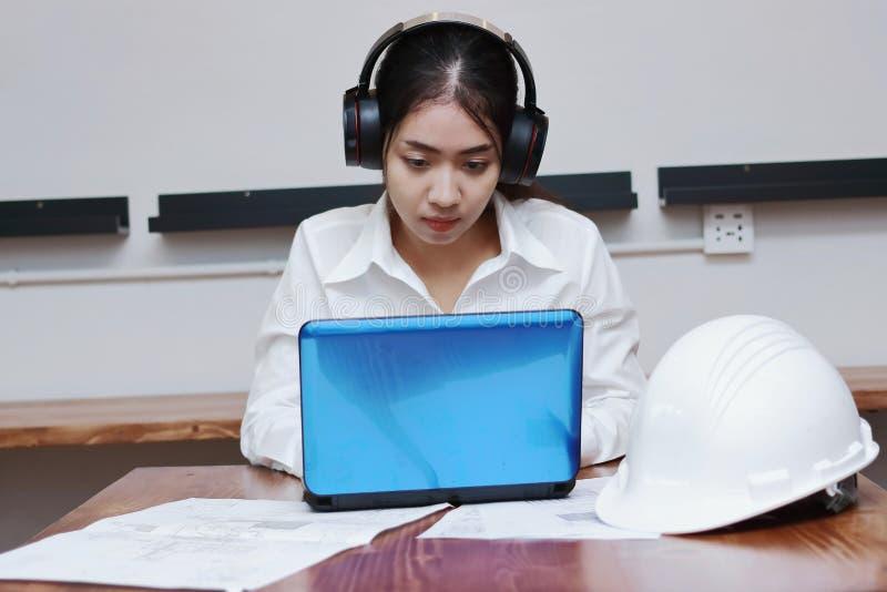 Avkopplat ungt asiatiskt arbete för affärskvinna och att lyssna musik med hörlurar i arbetsplats royaltyfri fotografi