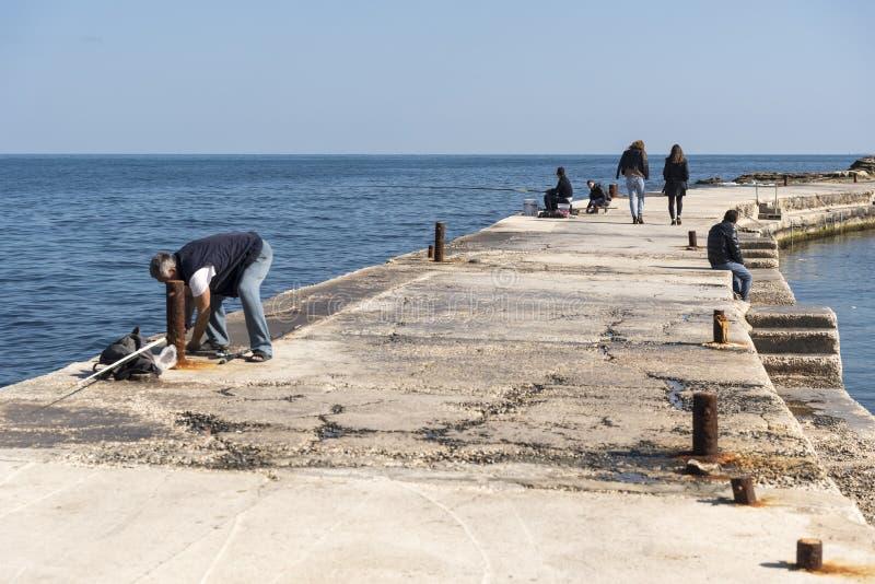 Avkoppling på vågbrytaren i Bugibba, St Pauls Bay Malta arkivfoton