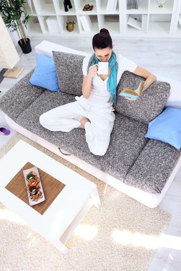 Avkopplingkvinna med tea och bok i vardagsrum royaltyfri bild