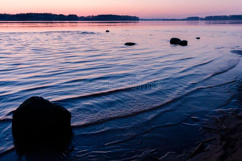 Avkopplinglandskap med en rosa solnedgång på en krabb flod och konturer av stora stenar arkivfoto