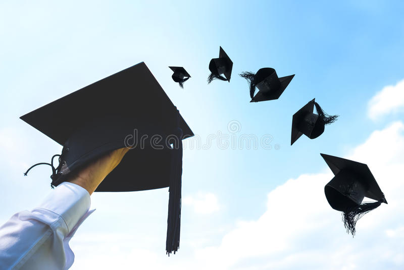 Avläggande av examendag, bilder av hållande lock för hand eller hatt som kastar i t arkivfoton