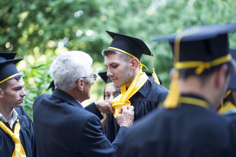 Avläggande av examendag på den lokala högstadiet i Rumänien royaltyfria foton