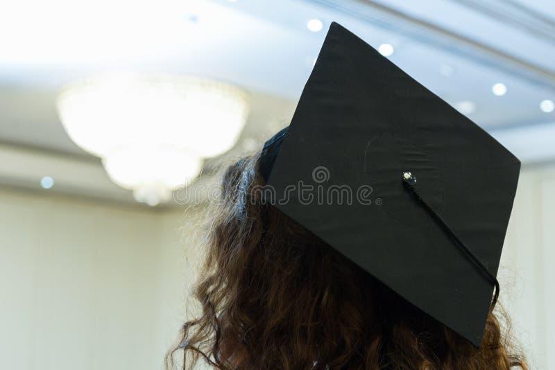 Avläggande av examenhatt arkivfoto
