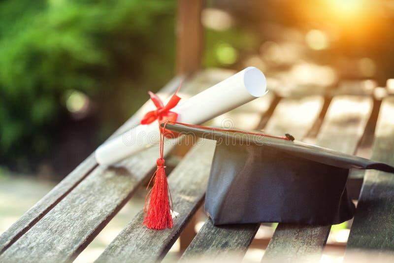Avläggande av examenhatt med tofsen, diplom med rött royaltyfria bilder