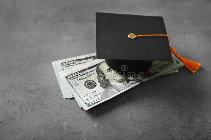 Avläggande av examenhatt- och dollarsedlar på tabellen royaltyfria bilder