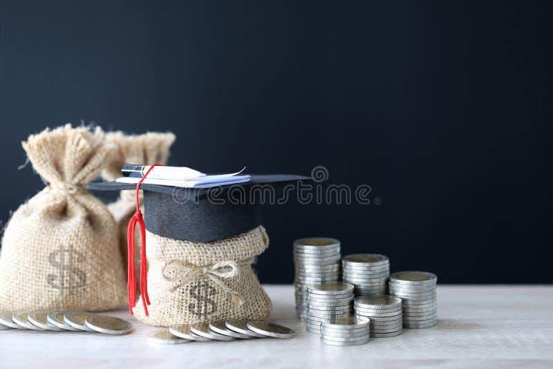 Avläggande av examenhatt på pengarpåsen med bunten av myntpengar på bla arkivfoton