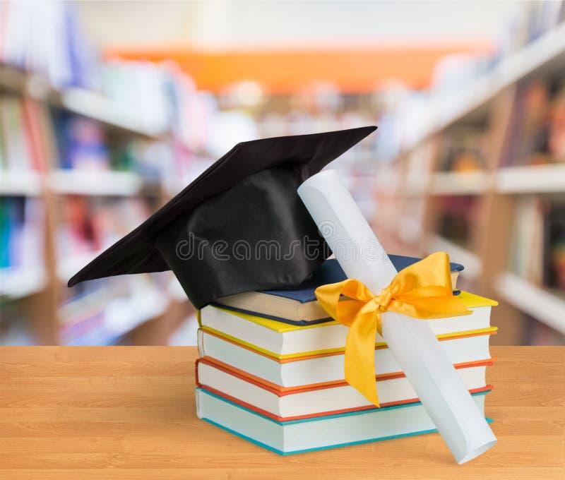 Avläggande av examenlock och böcker på tabellen arkivbild